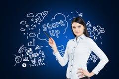 Donna che mostra schizzo startup sulla parete blu Immagine Stock