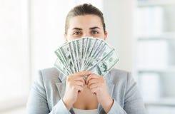Donna che nasconde il suo fronte dietro il fan dei soldi del dollaro americano Fotografie Stock
