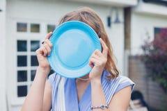 Donna che nasconde il suo fronte dietro il piatto blu Fotografie Stock Libere da Diritti