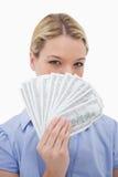 Donna che nasconde il suo fronte dietro soldi Fotografie Stock Libere da Diritti