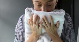 Donna che odora asciugamano pulito video d archivio