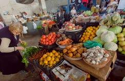 Donna che opera scelta sul mercato di verdure con il pomodoro fresco, il salat ed altri prodotti del ` s dell'agricoltore Immagini Stock