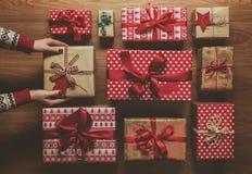 Donna che organizza i regali di Natale d'annata meravigliosamente avvolti, immagine con foschia, vista da sopra Immagini Stock