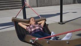 Donna che oscilla in amaca in parco moderno video d archivio