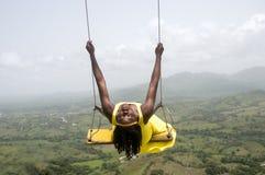 Donna che oscilla sopra le montagne fotografia stock libera da diritti