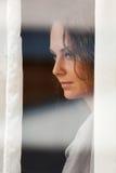 Donna che osserva attraverso la finestra Fotografie Stock Libere da Diritti