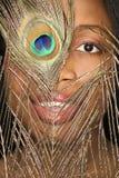 Donna che osserva attraverso la piuma. Immagine Stock