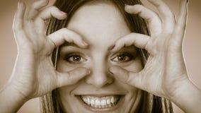 Donna che osserva con binoculare immaginario Fotografia Stock