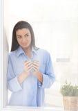 Donna che osserva dalla finestra con caffè Fotografie Stock Libere da Diritti