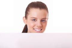 Donna che osserva dalla scheda in bianco Immagine Stock