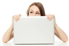 Donna che osserva fuori da dietro un computer portatile Fotografie Stock