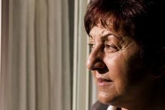Donna che osserva fuori la finestra Fotografie Stock Libere da Diritti