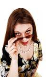 Donna che osserva sopra i suoi occhiali da sole. Fotografie Stock