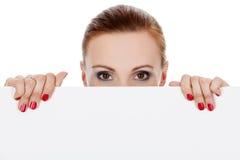 Donna che osserva sopra la priorità bassa bianca Fotografia Stock