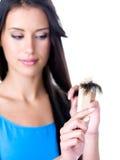 Donna che osserva sull'estremità di capelli immagine stock