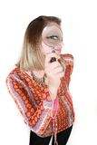 Donna che osserva tramite il magnifier sopra bianco fotografie stock libere da diritti