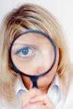 Donna che osserva tramite una lente d'ingrandimento Fotografia Stock