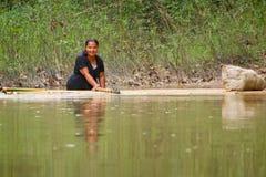 Donna che ottiene attraverso il fiume con la zattera Fotografie Stock