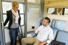 Donna che ottiene in compartimento del treno con l'uomo Immagine Stock