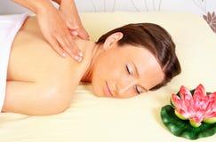 Donna che ottiene distendentesi nel salone di massaggio di bellezza Immagini Stock