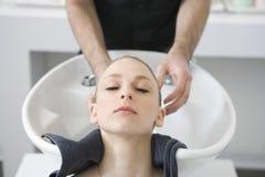 Donna che ottiene il lavaggio dei capelli dal parrucchiere in salone Fotografia Stock