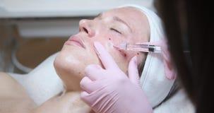 Donna che ottiene iniezione cosmetica di botox in guancia stock footage