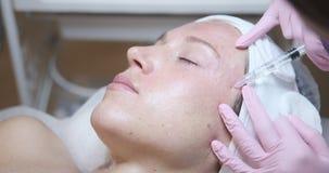 Donna che ottiene iniezione cosmetica in fronte stock footage