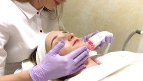 Donna che ottiene massaggio dell'hardware di GPL alla clinica di bellezza Funzionamento professionale dell'estetista video d archivio