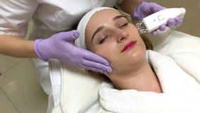 Donna che ottiene massaggio dell'hardware di GPL alla clinica di bellezza Funzionamento professionale dell'estetista stock footage