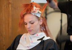 Donna che ottiene rosso tinto capelli fotografia stock