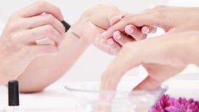 Donna che ottiene un manicure al salone dell'unghia video d archivio