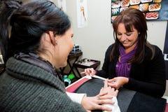 Donna che ottiene un manicure in barra cava chiodi del salone fotografie stock libere da diritti