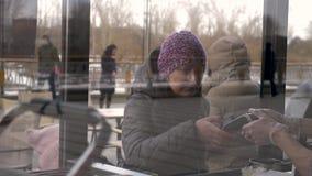 Donna che paga con la carta di credito sul terminale e sul hot dog d'acquisto, figlia che sta vicino stock footage