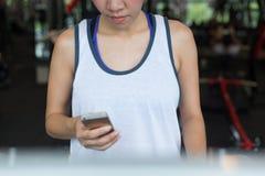 Donna che pareggia e che corre sulla cardio macchina della pedana mobile nella forma fisica Immagini Stock Libere da Diritti