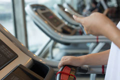 Donna che pareggia e che corre sulla cardio macchina della pedana mobile nella forma fisica Fotografia Stock