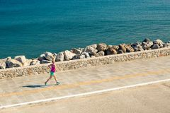 Donna che pareggia sulla via della città alla spiaggia Immagine Stock Libera da Diritti