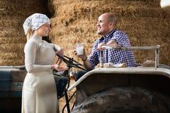 Donna che parla con l'agricoltore in trattore Fotografia Stock