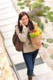 Donna che parla la borsa parlante di camminata del telefono astuto Fotografia Stock