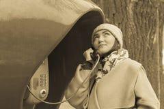 Donna che parla su un telefono pubblico rosso Retro tonificato fotografia stock libera da diritti