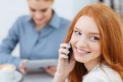 Donna che parla sul telefono cellulare che si siede con l'amico in caffè fotografia stock