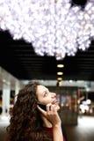Donna che parla sul telefono cellulare e che sorride all'aperto Fotografia Stock