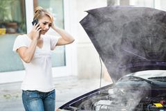 Donna che parla sul telefono cellulare in Front Of Car immagine stock