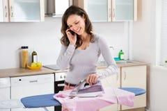 Donna che parla sul telefono cellulare mentre rivestendo di ferro fotografie stock libere da diritti