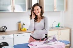 Donna che parla sul telefono cellulare mentre rivestendo di ferro immagini stock libere da diritti