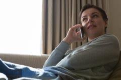 Donna che parla sul telefono cellulare in salone Immagine Stock