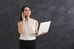 Donna che parla sul telefono e che tiene computer portatile Fotografia Stock Libera da Diritti