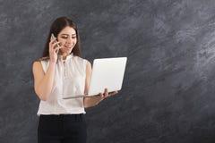 Donna che parla sul telefono e che tiene computer portatile Fotografie Stock Libere da Diritti