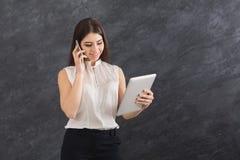 Donna che parla sul telefono e che tiene computer portatile Immagini Stock Libere da Diritti