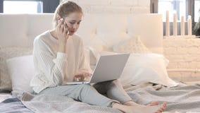 Donna che parla sul telefono mentre sedendosi a letto e per mezzo del computer portatile video d archivio