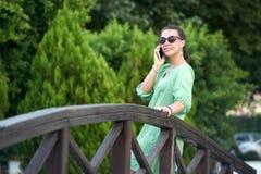 Donna che parla sul telefono nel parco fotografia stock